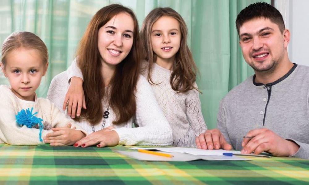 mother and father with two girls in he table helping with homework