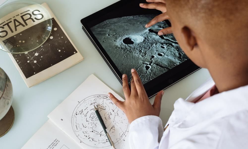 African American boy with star charts and tablet showing the moon.