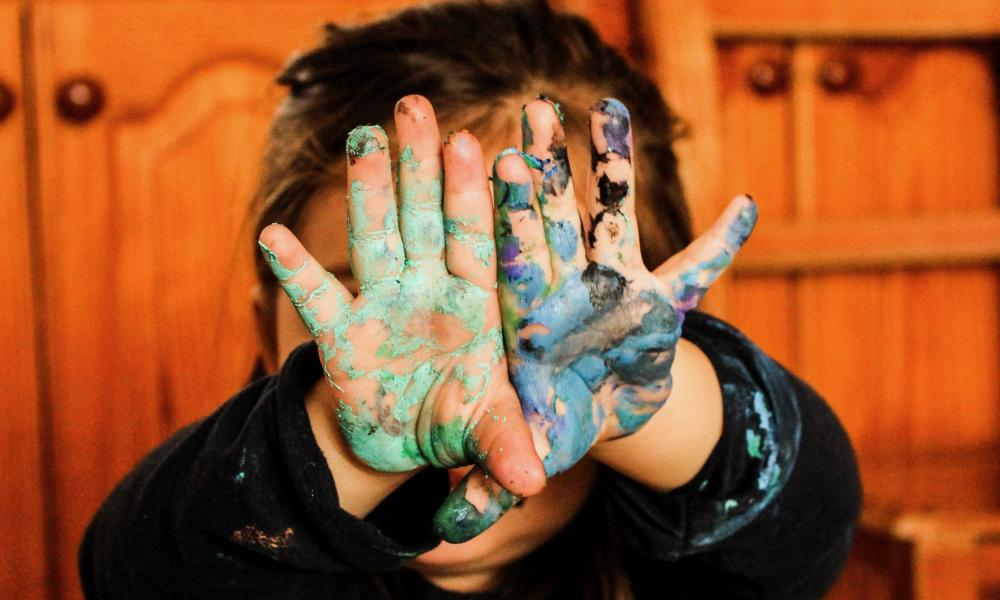 Child with painted hands in front of their face.
